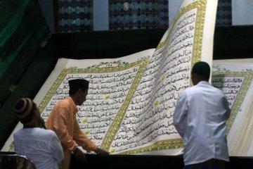 Membaca Al Quran ukuran besar