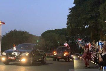 Pegawai Istana lambaikan bendera sambut kembalinya Jokowi ke istana