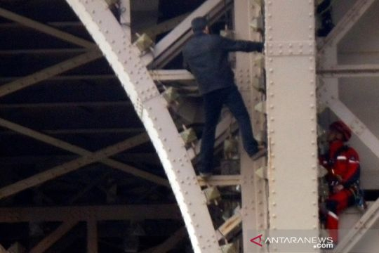 Seorang pria tak dikenal memanjat Menara Eiffel