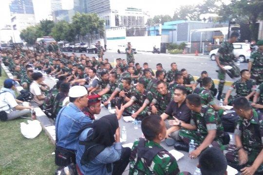 Personel TNI berbagi makanan buka puasa dengan peserta aksi 22 Mei