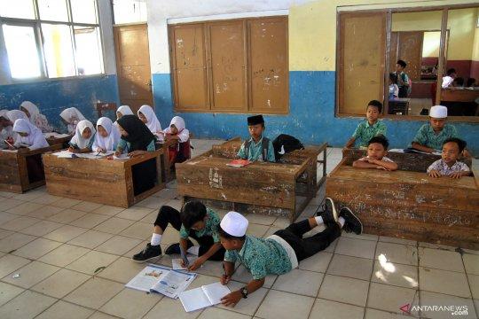 Siswa terpaksa belajar di lantai karena sekolah kekurangan bangku dan meja
