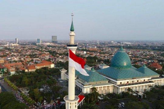 Bendera merah putih raksasa berkibar di menara Masjid Al Akbar