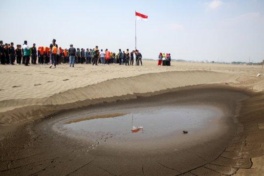 Pelajar NU Sidoarjo upacara bendera di kolam penampungan lumpur