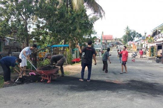 Warga Malanu Papua Barat membersihkan puing-puing pemalangan jalan