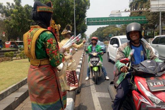 Puluhan wanita berbaju adat bagikan bunga di sekitar Patung Kuda