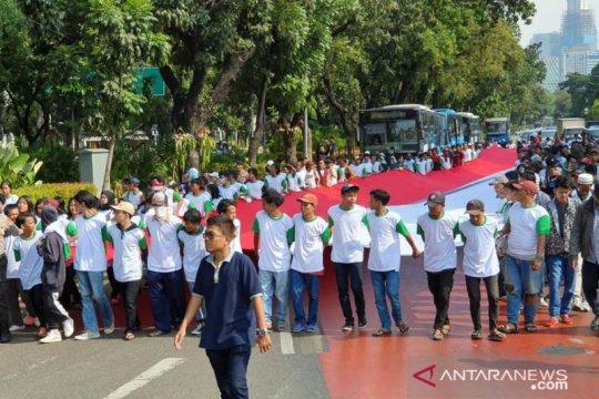 Bentangkan Merah Putih, massa dukung Jokowi lantik pimpinan baru KPK