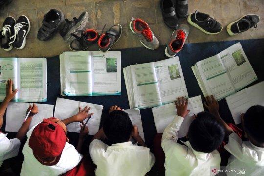 Kekurangan meja kursi, siswa belajar di lantai