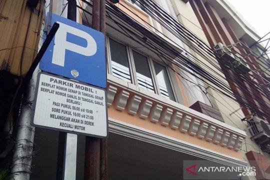 Petugas sosialisasi parkir ganjil genap ke pengemudi mobil