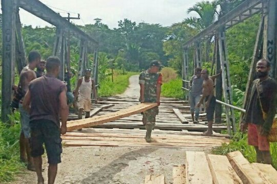 Babinsa Kemtuk Gresi bersama warga perbaiki jembatan