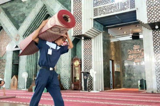 Pengurus Masjid Al Markaz bersihkan karpet antisipasi penularan Corona