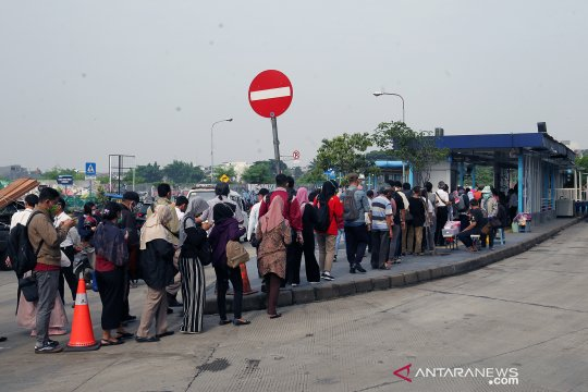Calon penumpang mengular saat antre naik TransJakarta