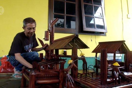 Merangkai bambu bekas menjadi kincir air yang menarik