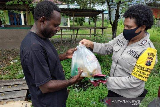 Petugas medis dan warga dibantu masker dan sembako Bhayangkari Mimika