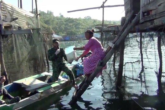 Aparat bagikan sembako gratis ke nelayan pesisir pakai perahu