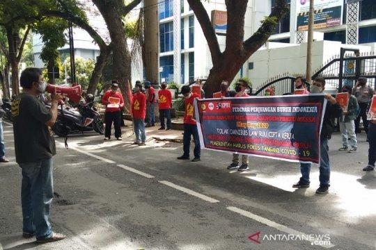 Para pekerja menjaga jarak aman dalam unjuk rasa Hari Buruh di Medan