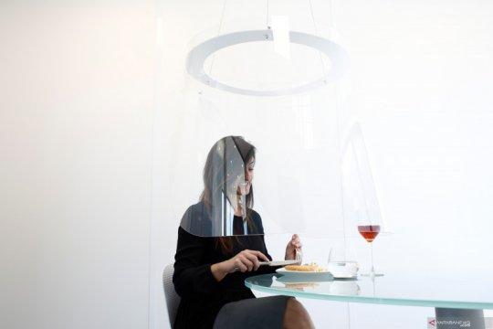 Plexiglas pelindung dari serangan COVID-19 saat makan malam di restoran di Paris