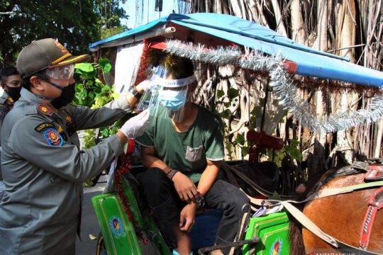 Pembagian pelindung wajah untuk pengemudi delman