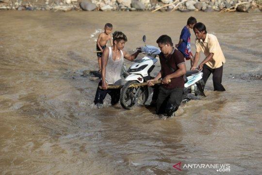 Jembatan hanyut terbawa banjir, warga terpaksa berjalan melintasi sungai