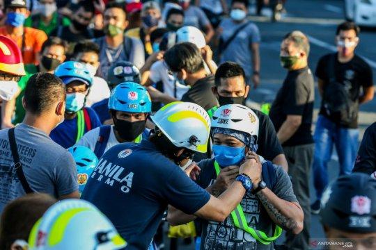 Pembagian helm gratis untuk pengendara sepeda di Manila