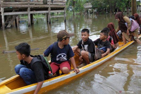 Anak-anak belajar kelompok di tengah banjir melanda