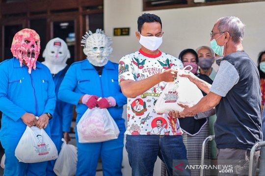 Berkostum monster corona, relawan Gibran bagikan sembako