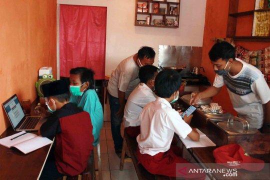 Akses internet gratis, murid belajar di sebuah warung kopi di Tangerang Selatan