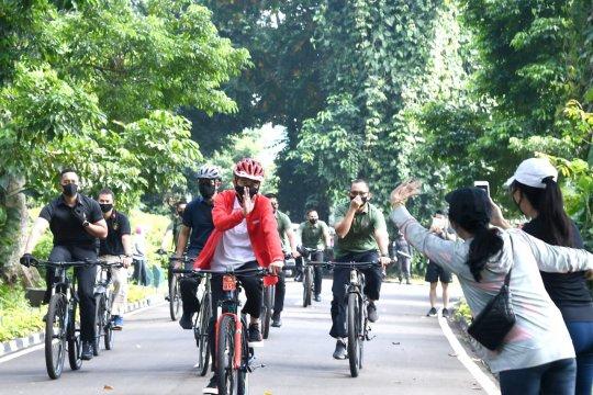 Presiden bersepeda sambil bagi-bagi masker di Kebun Raya Bogor