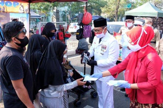 Polresta Sidoarjo kenakan pakaian pejuang sembari bagikan masker