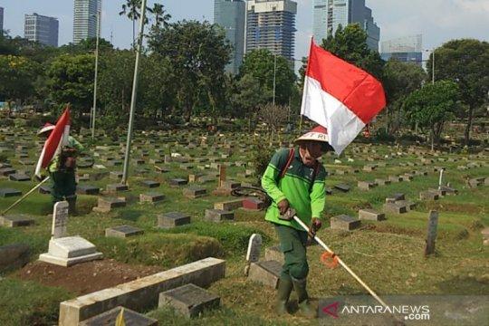 Sambut HUT RI, Petugas TPU Karet Bivak gendong bendera sambil kerja