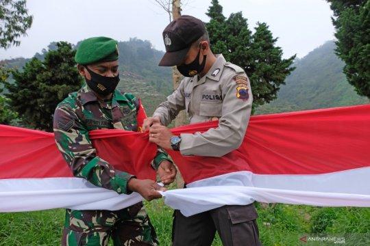 Pembentangan bendera merah putih untuk soliditas TNI dan Polri