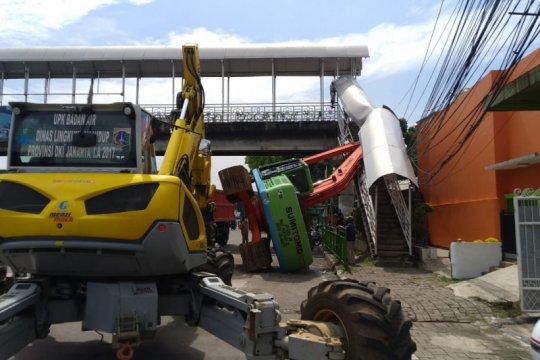 Alat berat terguling timpa pagar JPO Kampung Melayu