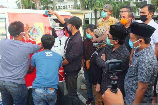 Plt Bupati-Bawaslu Jember tutup foto cabup petahana di ambulans desa