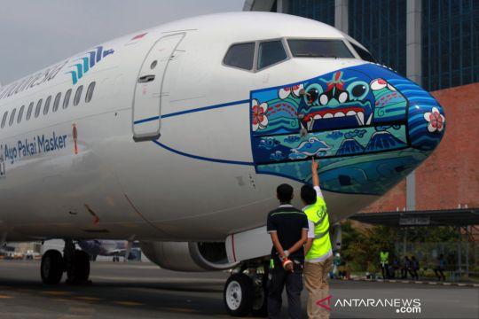 Gambar masker bertema Indonesia Pride di moncong pesawat Garuda Indonesia