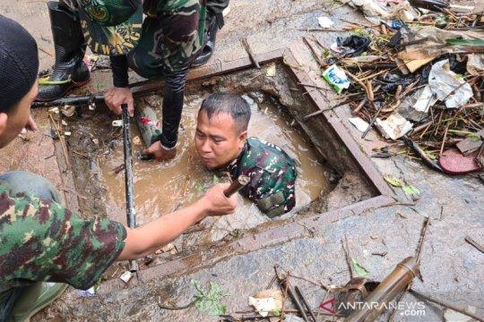 Anggota TNI menyelami parit untuk bersihkan sampah di Sumedang