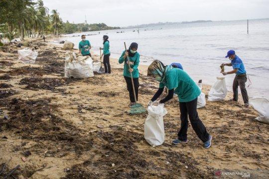 Bersih pantai yang tercemar limbah minyak hitam di Batam