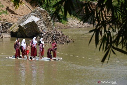 Warga menyeberangi sungai dengan rakit bambu
