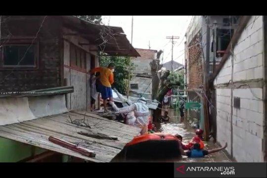 Petugas evakuasi seorang warga positif COVID-19 di tengah banjir
