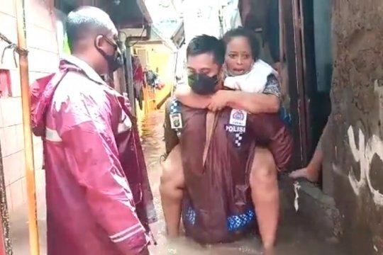 Kapolsek Cilandak gendong seorang nenek saat evakuasi banjir