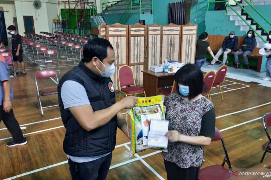 Polisi bagikan sembako kepada warga yang divaksin di GOR Makasar