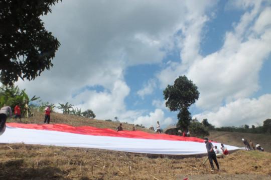 Warga Desa Lampeji Jember mengibarkan bendera merah putih raksasa