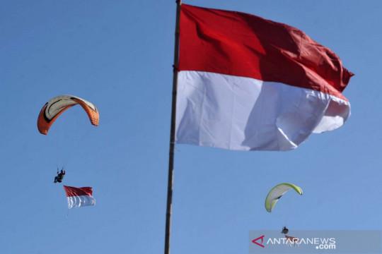 Pengibaran bendera Merah Putih di langit Bali dengan paralayang