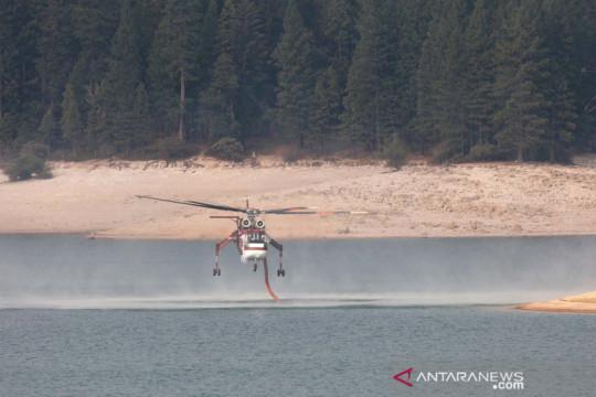Helikopter Skycrane mengisi air saat operasi pemadaman kebakaran hutan di California