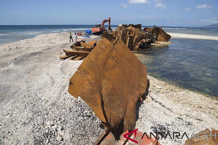Pekerja mengoperasikan alat berat untuk mengevakuasi bagian potongan badan kapal tongkang batu bara yang terdampar di Pantai Wisata Lhokseudu, Lhoknga, Kabupaten Aceh Besar, Aceh,Sabtu (12/1/2019). Evakuasi kapal tongkang yang kandas pada 27 Juli 2018 itu dilakukan dalam upaya pemulihan ekosistim pantai dan terumbu karang, termasuk pembersihan tumpahan batu bara yang masih tersisa sekitar 1.000 ton dari total 8.000 ton yang tumpah mencemari peraian pantai. (Antara Aceh/Ampelsa)