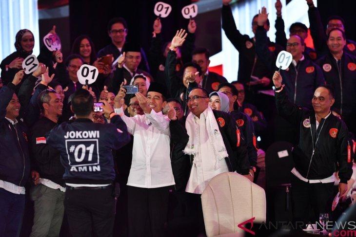 Jeda debat, Sandiaga pijat Prabowo dan Jokowi asik berfoto