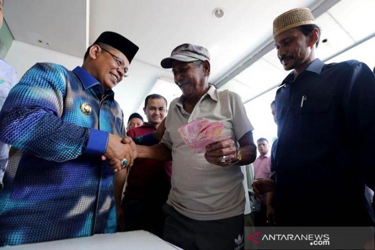 Walikota Banda Aceh Aminullah Usman (kiri) menyerahkan zakat konsumtif dan senif dari lembaga penyaluran zakat Baitul Mal kepada warga penerima di halaman Balaikota, Banda Aceh, Sabtu (25/5/2019). Baitul Mal kota Banda Aceh menyalurkan total Rp4,2 miliar untuk 7.265 orang dengan kategori fakir, miskin, anak yatim, penyandang disabilitas dan petugas kebersihan dengan kisaran antara Rp250 ribu hingga Rp1 juta per orang. (Antara Aceh/Irwansyah Putra)