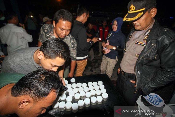 Petugas gabungan Badan Narkotika Nasioal (BNN) dan Polisi satuan narkoba mememeriksa urine para Sopir Bus Antar Kota Antar Provinsi (AKAP) di terminal tipe A Lhokseumawe, Aceh, Jumat (31/5/2019) tengah malam. Pemeriksaan urine mendadak sopir dan kernet AKAP itu bertujuan mengantisipasi pemakaian narkoba dan alkohol guna memberikan rasa aman dan nyaman pemudik dari Aceh. (Antara Aceh/Rahmad)