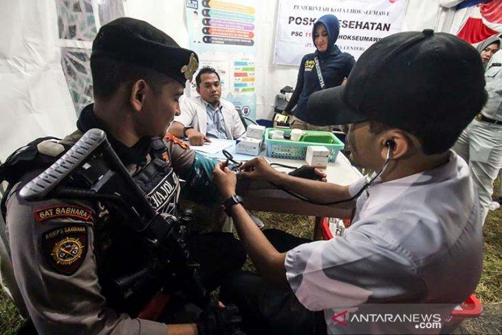 Personel Kepolisian menjalani pemeriksaan Kesehatan di posko pengobatan gratis Jasa Raharja di Lhokseumawe, Aceh, Jumat (31/5/2019) malam. Pemeriksaan kesehatan dengan memberikan suplai obat dan vitamin itu di lakukan untuk memastikan jika personel Polri masih dalam keadaan sehat fisik dan mental dalam melaksanakan tugas pengamanan mudik dan lebaran di Aceh. (Antara Aceh/Rahmad)