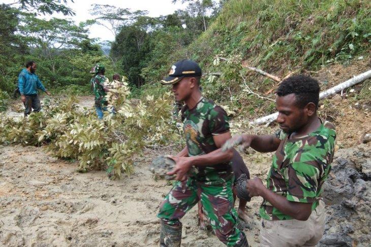Yonif 725/WRG bersama warga membersihkan jalan akibat longsor