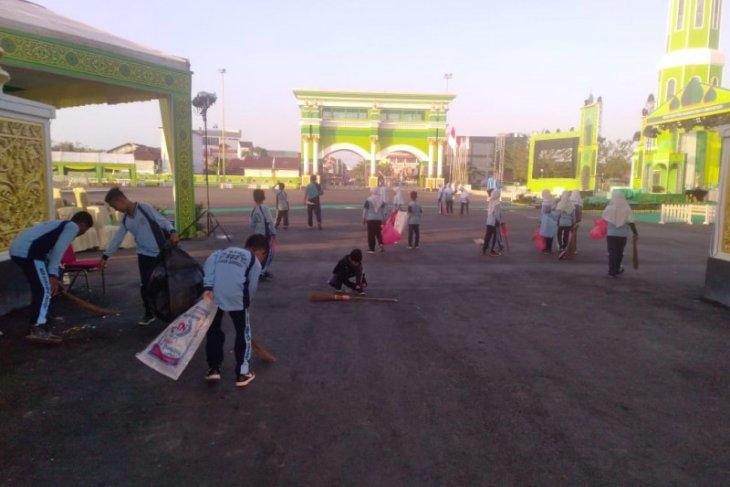 Siswa SD Bersihkan Arena Utama Kegiatan MTQKaltim