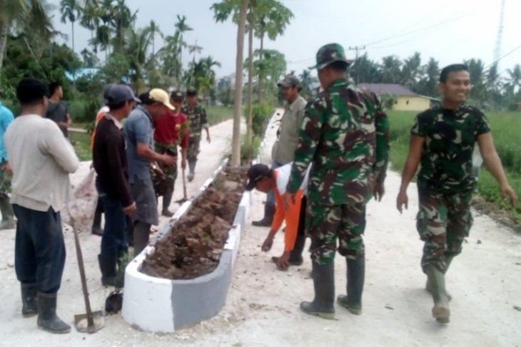 Satgas TMMD Kodim Inhil Menanam Bunga Asoka Di Poros Jalan Tengah